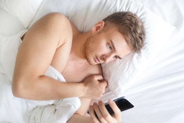Przystojny facet, młody poważny skoncentrowany mężczyzna na czacie, wpisując wiadomość patrząc na komórkę inteligentny telefon w łóżku, sypialnia przed snem, leżąc na poduszce z kocem. uzależnienie od mediów społecznościowych