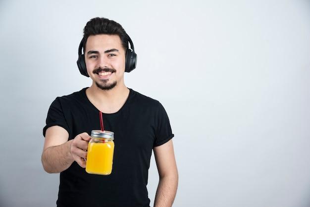 Przystojny facet model w słuchawkach pokazując szklany kubek z sokiem pomarańczowym do aparatu.