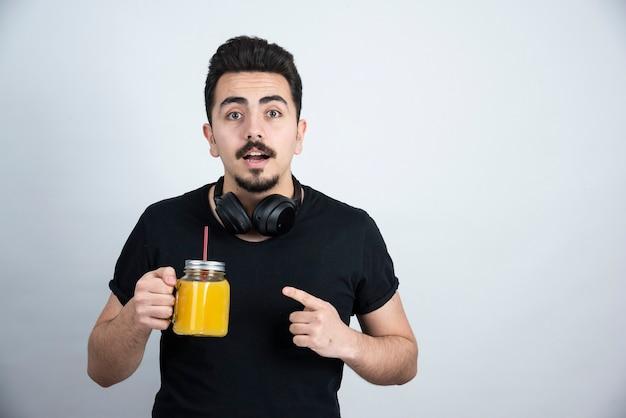 Przystojny facet model w słuchawkach, trzymając szklany kubek z sokiem pomarańczowym.