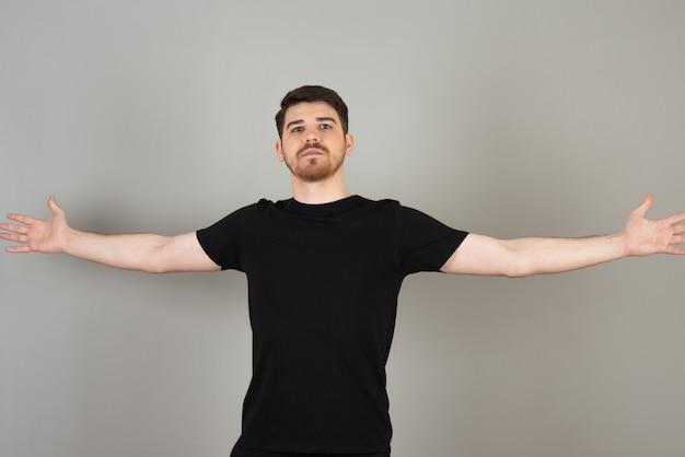 Przystojny facet na szaro szeroko otwiera ramiona.