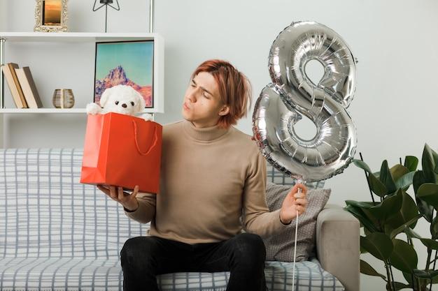 Przystojny facet na szczęśliwy dzień kobiet, trzymając balon numer osiem, patrząc na torbę z prezentami w ręku, siedząc na kanapie w salonie