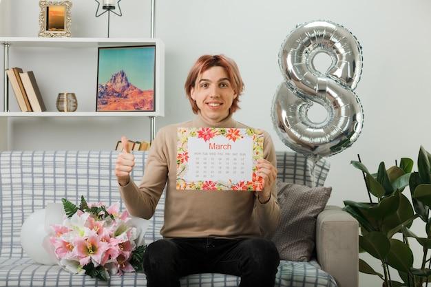 Przystojny facet na szczęśliwy dzień kobiet trzymając kalendarz siedzący na kanapie w salonie