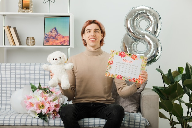 Przystojny facet na szczęśliwy dzień kobiet, trzymając misia z kalendarzem, siedząc na kanapie w salonie