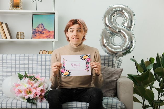 Przystojny facet na szczęśliwy dzień kobiet trzymając pocztówkę, siedząc na kanapie w salonie