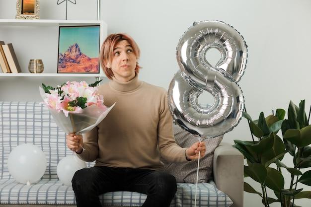 Przystojny facet na szczęśliwy dzień kobiet trzymający balon numer osiem i bukiet siedzący na kanapie w salonie
