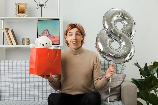 Przystojny facet na szczęśliwy dzień kobiet trzymający balon numer osiem z torbą na prezenty siedzący na kanapie w salonie