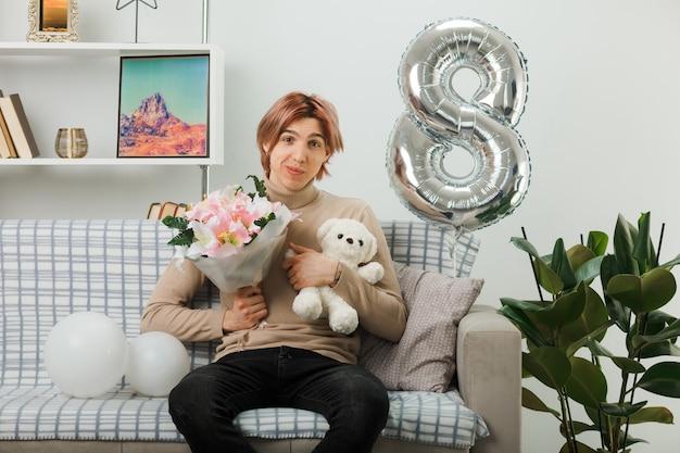 Przystojny facet na szczęśliwy dzień kobiet trzymający bukiet z misiem siedzącym na kanapie w salonie