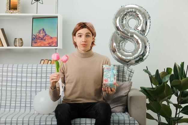 Przystojny facet na szczęśliwy dzień kobiet trzymający kwiaty z obecnym siedzącym na kanapie w salonie