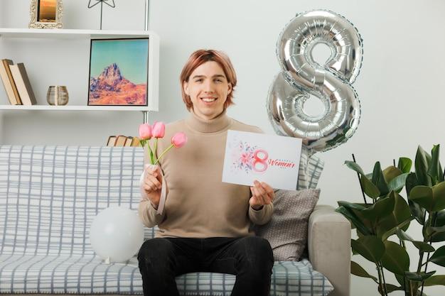 Przystojny facet na szczęśliwy dzień kobiet trzymający kwiaty z pocztówką, siedząc na kanapie w salonie
