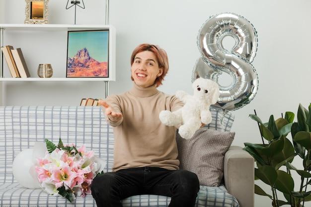 Przystojny facet na szczęśliwy dzień kobiet trzymający misia siedzącego na kanapie w salonie