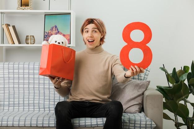 Przystojny facet na szczęśliwy dzień kobiet trzymający numer osiem z torbą na prezenty siedzący na kanapie w salonie