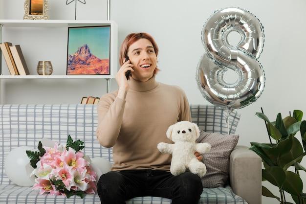 Przystojny facet na szczęśliwy dzień kobiet trzymający pluszowego misia mówi na telefonie, siedząc na kanapie w salonie