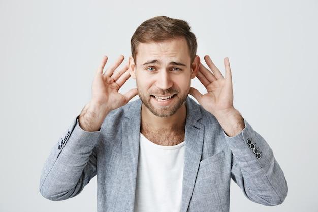 Przystojny facet nic nie słyszy, trzymaj ręce przy uszach