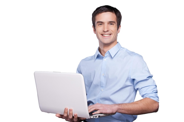 Przystojny facet od komputera. przystojny młody mężczyzna w niebieskiej koszuli trzyma laptopa i uśmiecha się stojąc na białym tle