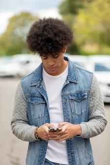 Przystojny facet patrząc na telefon komórkowy