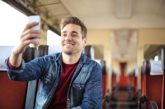 Przystojny facet podróżujący pociągiem, biorąc selfie