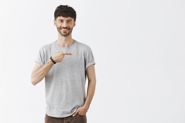 Przystojny facet pozuje przy białej ścianie