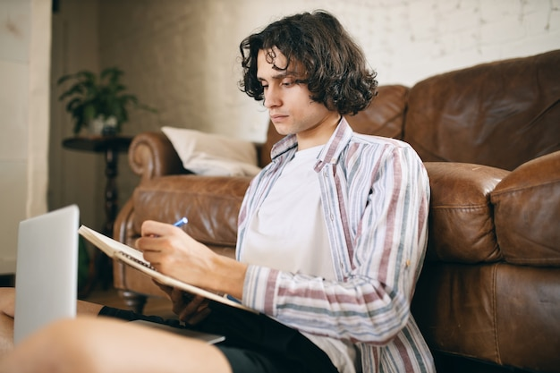 Przystojny facet siedzi na podłodze i robi notatki podczas słuchania kursu edukacyjnego, studiuje online. poważny facet pracujący w domu