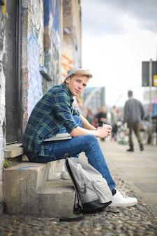 Przystojny facet siedzi na ulicy, pijąc kawę