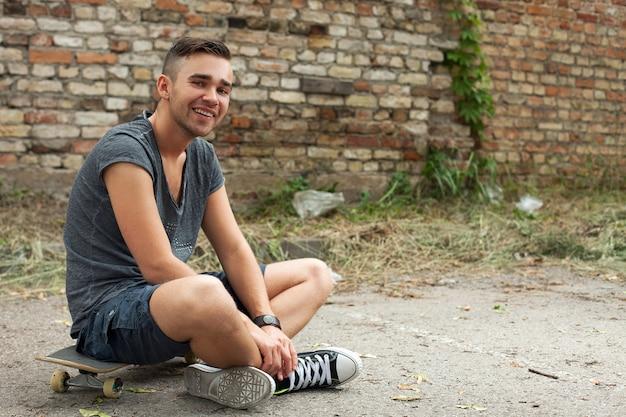 Przystojny facet siedzi na ulicy