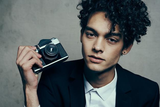 Przystojny facet w garniturze z aparatem lekcje kręcone włosy model emocji