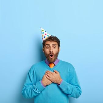 Przystojny facet w kapeluszu urodziny pozowanie w niebieskim swetrze