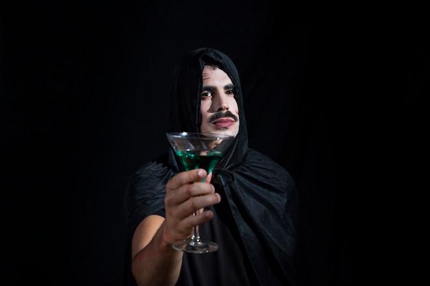 Przystojny facet w kapturze z wineglass