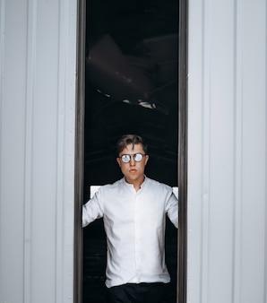 Przystojny facet w okularach przeciwsłonecznych otwiera drzwi do hangaru.