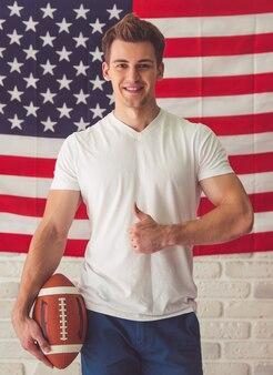 Przystojny facet w przypadkowych ubraniach trzyma futbolową piłkę.