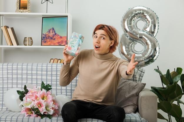 Przystojny facet w szczęśliwy dzień kobiet trzyma prezent siedzący na kanapie w salonie