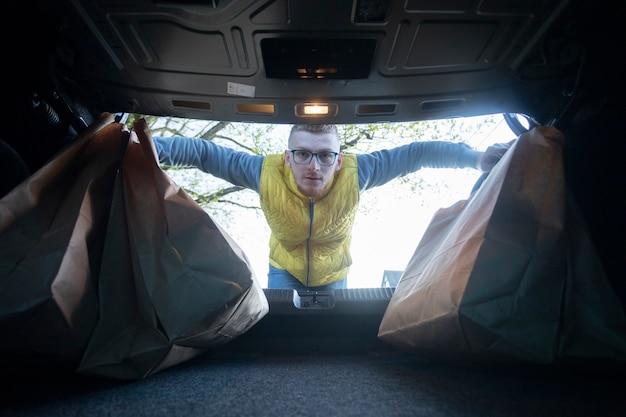 Przystojny facet wkłada papierowe torby do bagażnika samochodu po zakupach w supermarkecie