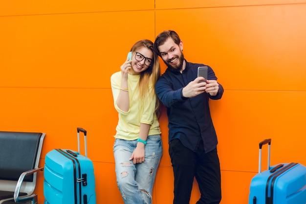 Przystojny facet z brodą w czarnej koszuli ze spodniami robi selfie-portret z ładną dziewczyną w pobliżu na pomarańczowym tle między dwiema walizkami. ma długie włosy, sweter, dżinsy i rozmawia przez telefon