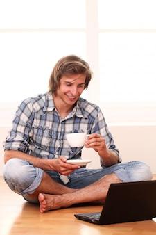 Przystojny facet z filiżanką kawy i laptopem