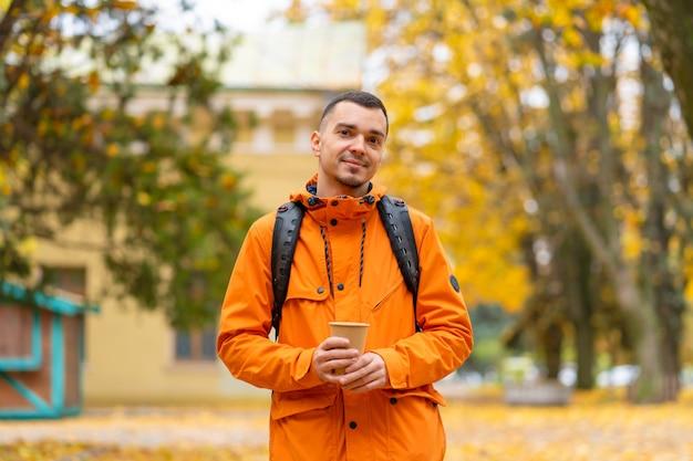 Przystojny facet z filiżanką kawy kraft, ironiczny portret w jesiennym parku.