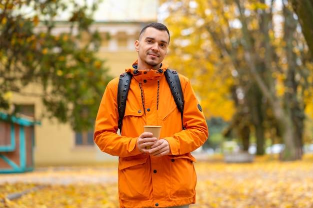 Przystojny facet z filiżanką kawy kraft, ironiczny portret w jesiennym parku