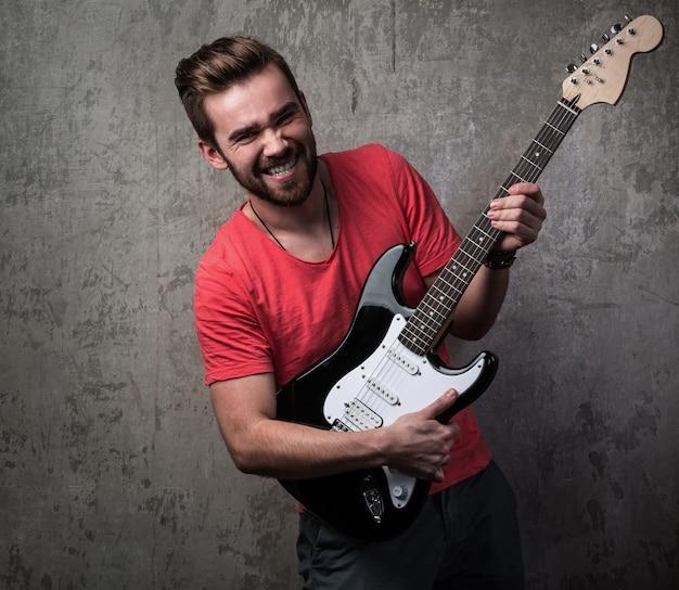 Przystojny facet z gitarą elektryczną