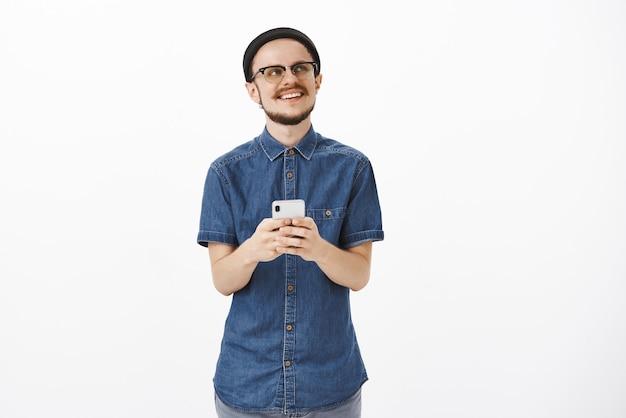 Przystojny facet z nostalgią wspominający wspaniały moment z wakacji podczas przewijania zdjęć z wakacji patrząc w prawy górny róg rozmarzony i zachwycony radosnym uśmiechem