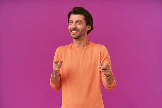 Przystojny, fajny mężczyzna z brunetką i włosiem. ubrana w pomarańczowy sweter z podwiniętymi rękawami. posiada bransoletki, pierścionki. wskazuje na ciebie palcami