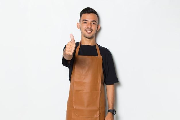 Przystojny fartuch mężczyzna uśmiechający się dumny i zadowolony z ok gestem gestem tumb na białym tle