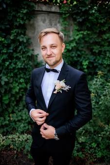 Przystojny fornal w czarnym kostiumu i biel róży boutonniere stojakach w ogródzie
