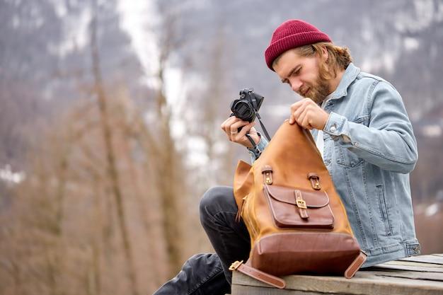 Przystojny fotograf kaukaski mężczyzna biorący aparat ze skórzanego ręcznie robionego plecaka, zamierzający robić zdjęcia. fotografia, koncepcja ręcznie robionych akcesoriów. kopiuj przestrzeń