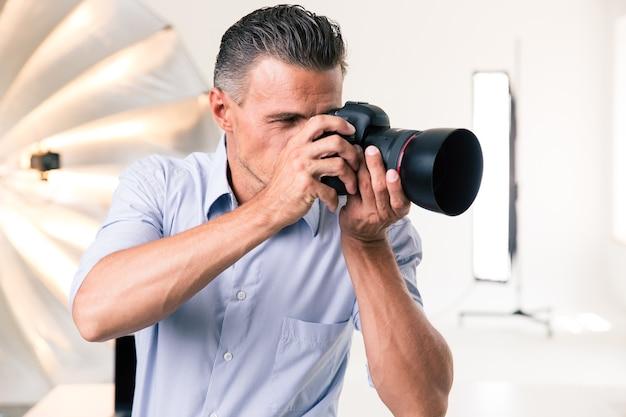 Przystojny fotograf robiący zdjęcie w aparacie w studio