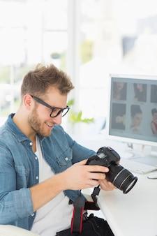 Przystojny fotograf trzyma jego kamerę i ono uśmiecha się
