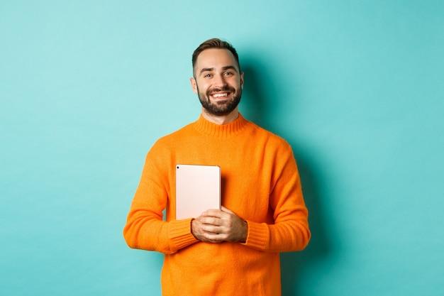 Przystojny freelancer mężczyzna trzyma laptop i uśmiecha się, stoi szczęśliwy nad jasną turkusową ścianą
