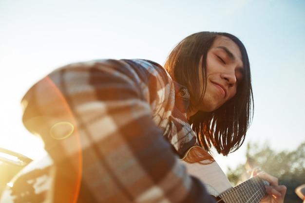 Przystojny gitarzysta korzystających letni dzień