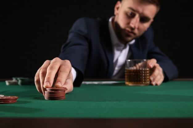 Przystojny gracz w pokera przy stole w kasynie