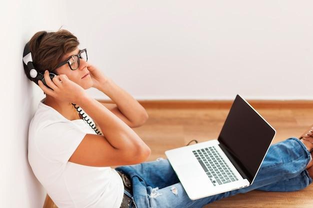 Przystojny hipster siedzi przed ścianą, słuchając muzyki