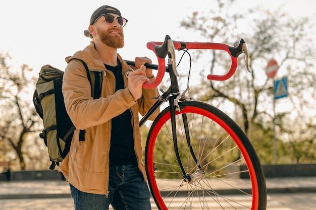 Przystojny hipster stylowy brodaty mężczyzna w kurtce i okularach przeciwsłonecznych spacerujący samotnie na ulicy z plecakiem na rowerze podróżnik z plecakiem zdrowego, aktywnego stylu życia