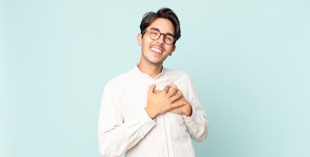 Przystojny hiszpan czuje się romantyczny, szczęśliwy i zakochany, uśmiechając się radośnie i trzymając ręce blisko serca