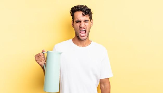 Przystojny hiszpan krzyczy agresywnie, wygląda na bardzo zły. koncepcja termosu do kawy